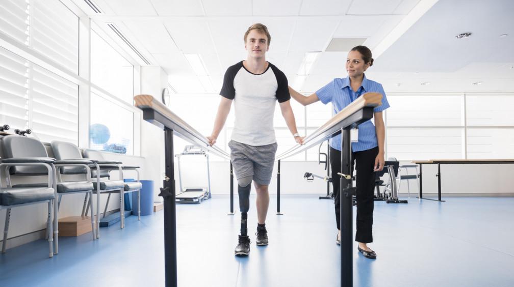 Man with prosthetic leg using parallel b.. 2 invalid na begovoj dorozhke e1569230003633