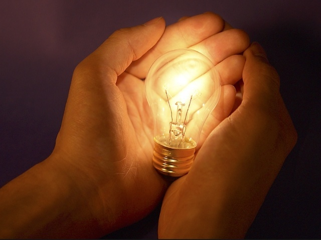 Лампа накаливания в руках человека