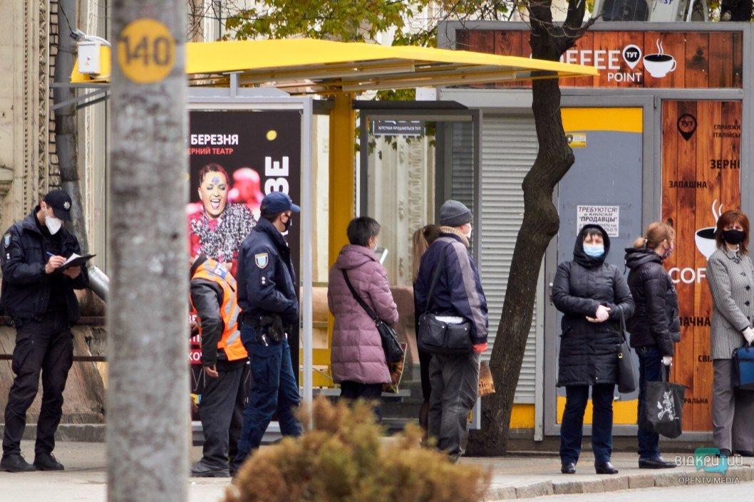 Люди на остановке в масках в Днепре