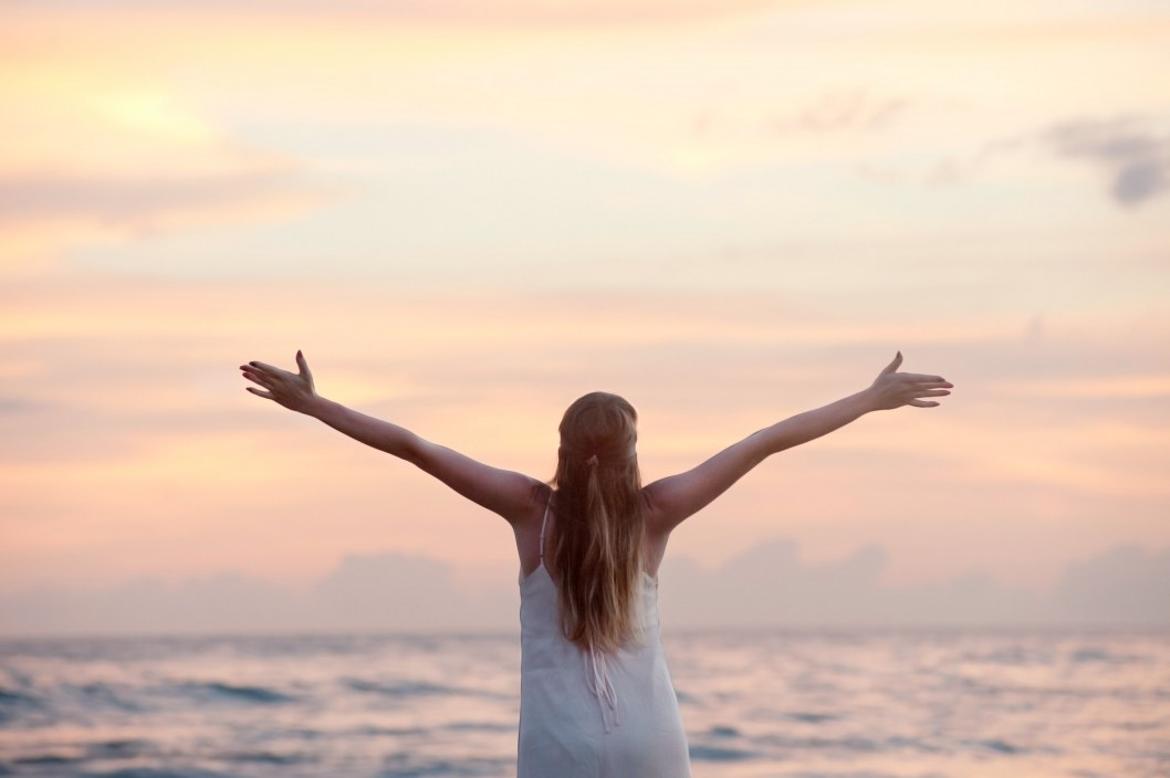 rear view of woman with arms raised at beach during sunset 320007
