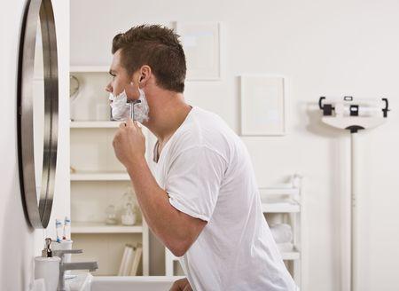 5333345 een jonge man is scheren zijn gezicht voor de badkamerspiegel hij kijkt weg van de camera horizontaa